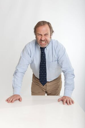 angry businessman: Angry looking business man leaning on a table