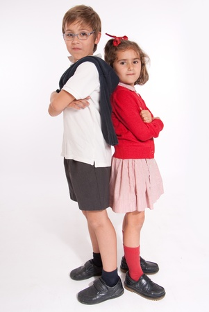 A boy  and little girl back to back with annoyed expressions photo