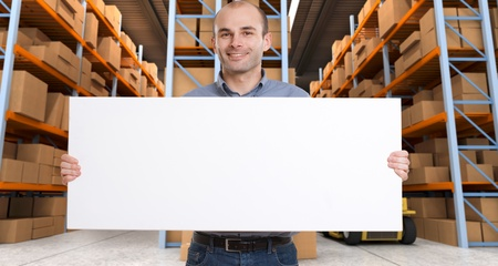 A man holding a blank board in a distribution warehouse, ideal for inserting your own message Stock Photo - 13569069