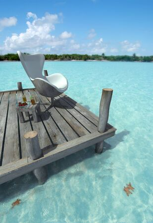 Designers chair on a peer, side table with refreshments and a beautiful Caribbean ocean Stock Photo - 13496711