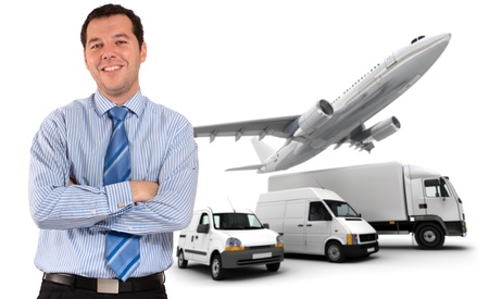 Happy businessman standing against a transportation fleet photo