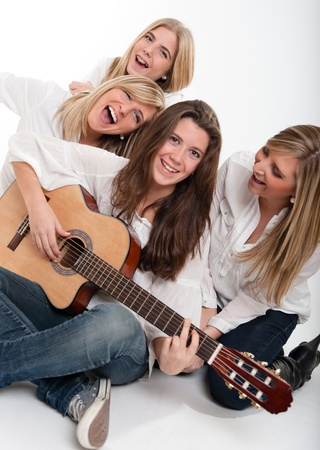 playing folk:  A group of girls singing accompanied by a guitar