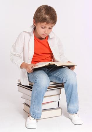 diligente: Colegial sentado sobre una pila de libros de lectura de un grande