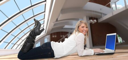 e work: Young woman on an empty spacious loft using a laptop lying on the floor