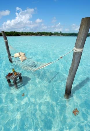 hamaca: Hamaca que cuelga sobre el agua del mar tropical, y una mesa con refrescos