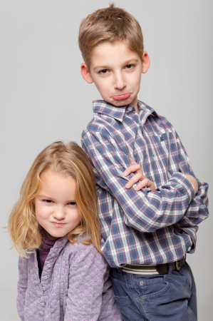 Boy and little girl with very angry expressions photo
