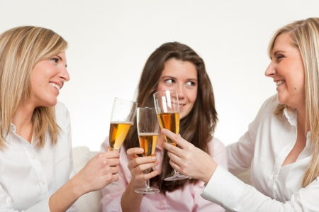 Three young female friends toasting with flutes photo
