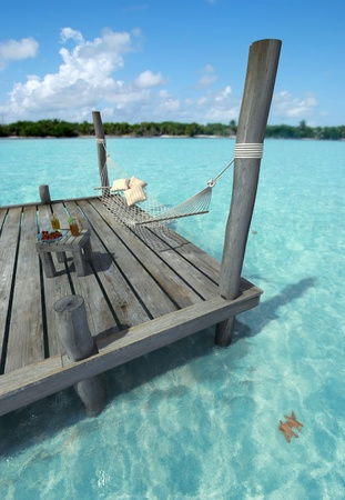caribbean drink: Hammock swinging in a pier by a tropical landscape, with a side table laden with fruits and refreshments Stock Photo
