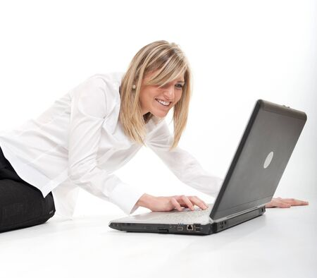 Attractive happy young blonde using a laptop on the floor Stock Photo - 13682443