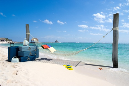 A hanging hammock, a pile of luggage, thongs and starfish on a beach resort photo