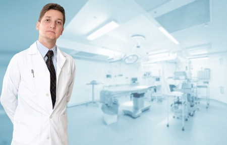 operating theater: Serious male doctor with an operating room at the background Stock Photo