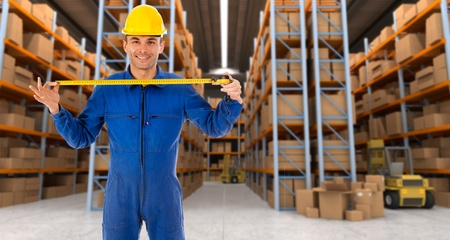 cinta metrica: Hombre con casco y un mono azul en un almac�n de distribuci�n que se extiende una cinta m�trica Foto de archivo