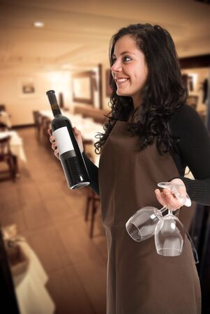 Smiling female sommelier presenting a wine bottle with a blank label and a pair of glasses in a restaurant photo