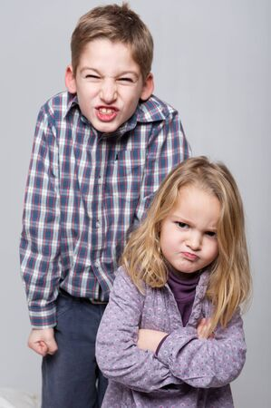 brother sister fight:  Boy and little girl with very angry expressions  Stock Photo