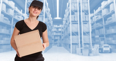 Female courier carrying a parcel in a distribution warehouse Stock Photo - 13734510