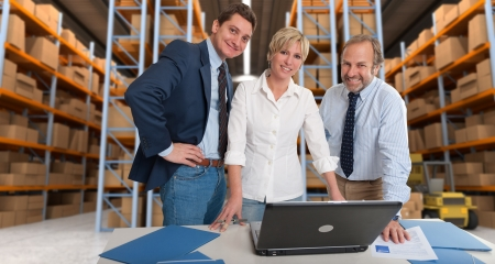 order shipment: Business team with a storage warehouse at the background Stock Photo