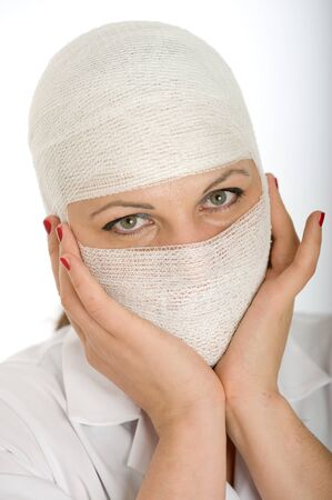 Close-up portrait of a woman with a bandaged head and face   photo