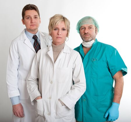 Serious looking medical staff team with a surgeon a practitioner and a nurse  photo