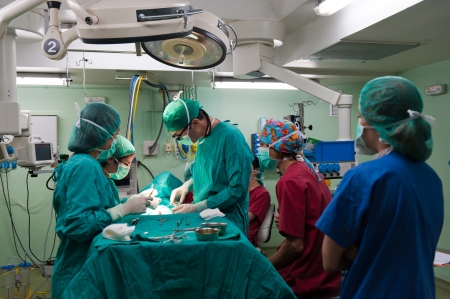 operation lamp: Medical team performing surgery on a young patient