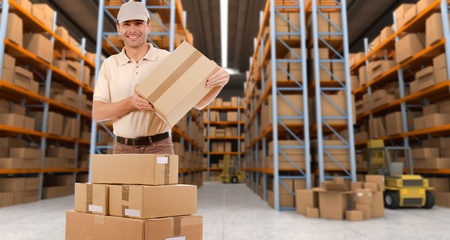 Delivery man carrying a parcel in a distribution warehouse photo