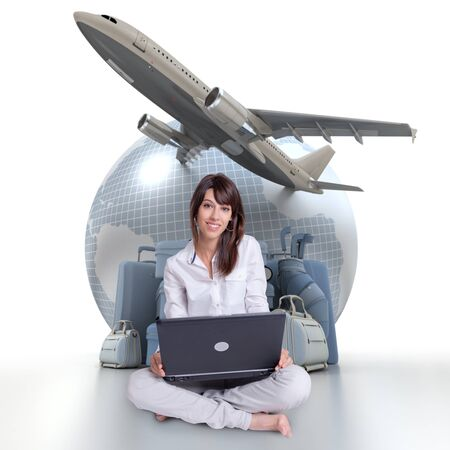 Young brunette sitting with a laptop with an Earth a plane taking off and a pile of luggage in the background photo