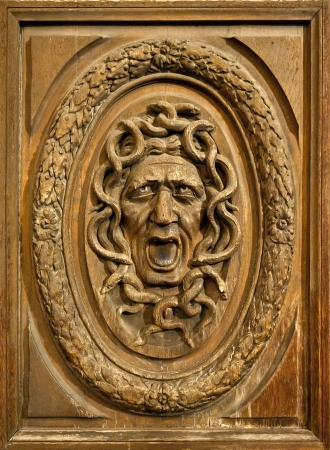 wood carving: Medusa head carved on a wooden door