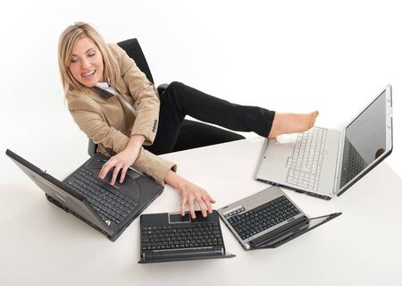 feet on desk:  Young women in a desk overcrowded with computers typing with both hands and feet