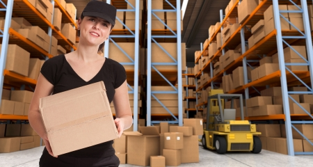 Female courier carrying a parcel in a distribution warehouse photo