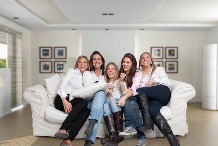 A group of five happy women of different ages laughing in the living room photo