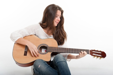 playing folk:  Cute brunette girl playing the guitar  Stock Photo