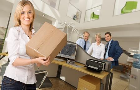 Mujer joven con una caja en un hermoso interior de la oficina Foto de archivo