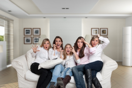 A group of five women of different ages sitting on the livingroom looking at the camera with scared expressions Stock Photo - 13953925