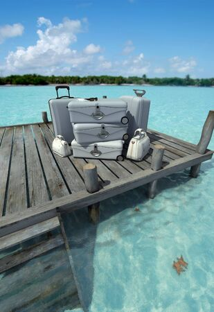 A pile of luxurious luggage standing by the pier on a tropical landscape photo