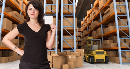 distribution board: A woman holding a blank paper in a distribution warehouse, ideal for inserting your own message Stock Photo