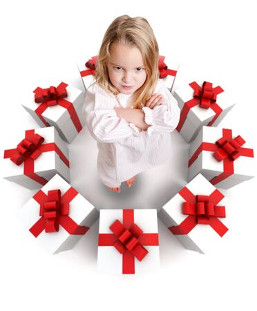 nighttimes: Sulking funny little girl in pajamas surrounded by a ring of presents Stock Photo