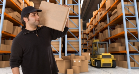 man carrying box: Deliveryman carrying a parcel in a distribution warehouse