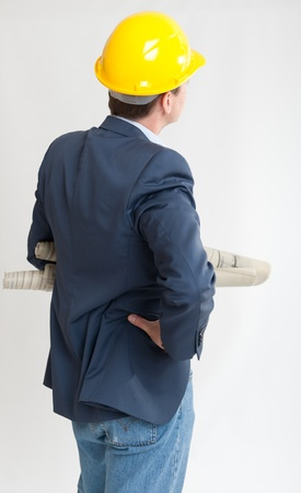man rear view:  Rear view of a man with a safety helmet consulting blueprints  Stock Photo