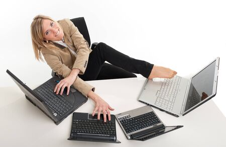 Young women in a desk overcrowded with computers typing with both hands and feet Stock Photo - 14056891