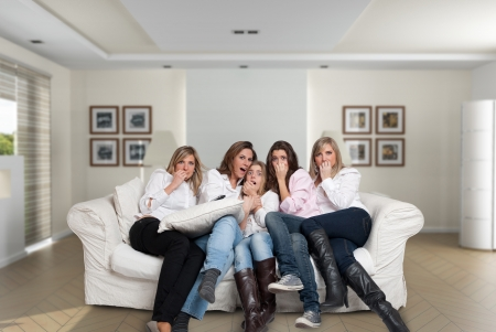 A group of five women of different ages sitting on the livingroom looking at the camera with scared expressions photo