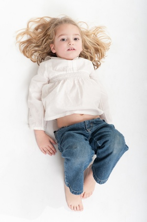 Aerial view of a cute little girl posing on the floor  photo