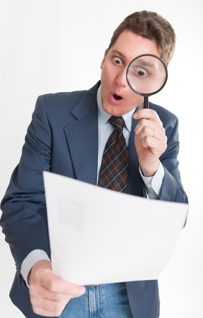 Young businessman looking to a document through a magnifying glass   Stock Photo - 14230264
