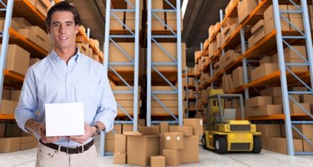 carretillas almacen: Hombre joven con una caja en blanco en un almacén de distribución