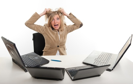 panicked:  Panicked young woman in front of four laptops
