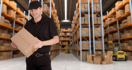 order shipment: Deliveryman carrying a parcel in a distribution warehouse