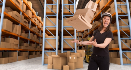 Stressed woman with helmet trying to catch flying parcels in a warehouse photo