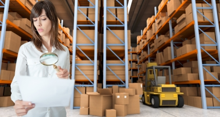 Young woman verifying document with magnifying glass in a distribution warehouse photo