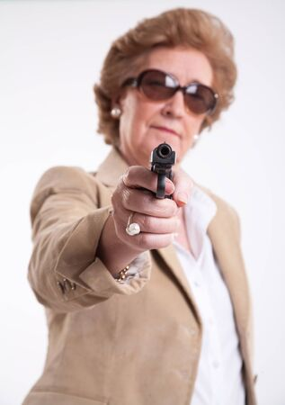Mature lady with sunglasses and a gun in her hand  photo