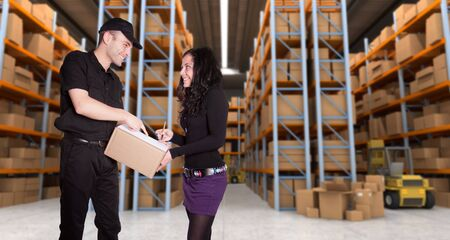 order shipment: Worker delivering a parcel to young woman in a distribution warehouse
