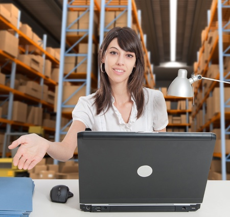 Female administrative in a desk with a distribution warehouse in the background photo