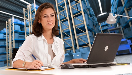 Business administration: Administrativa Mujer en un escritorio con un almac�n de distribuci�n en el fondo